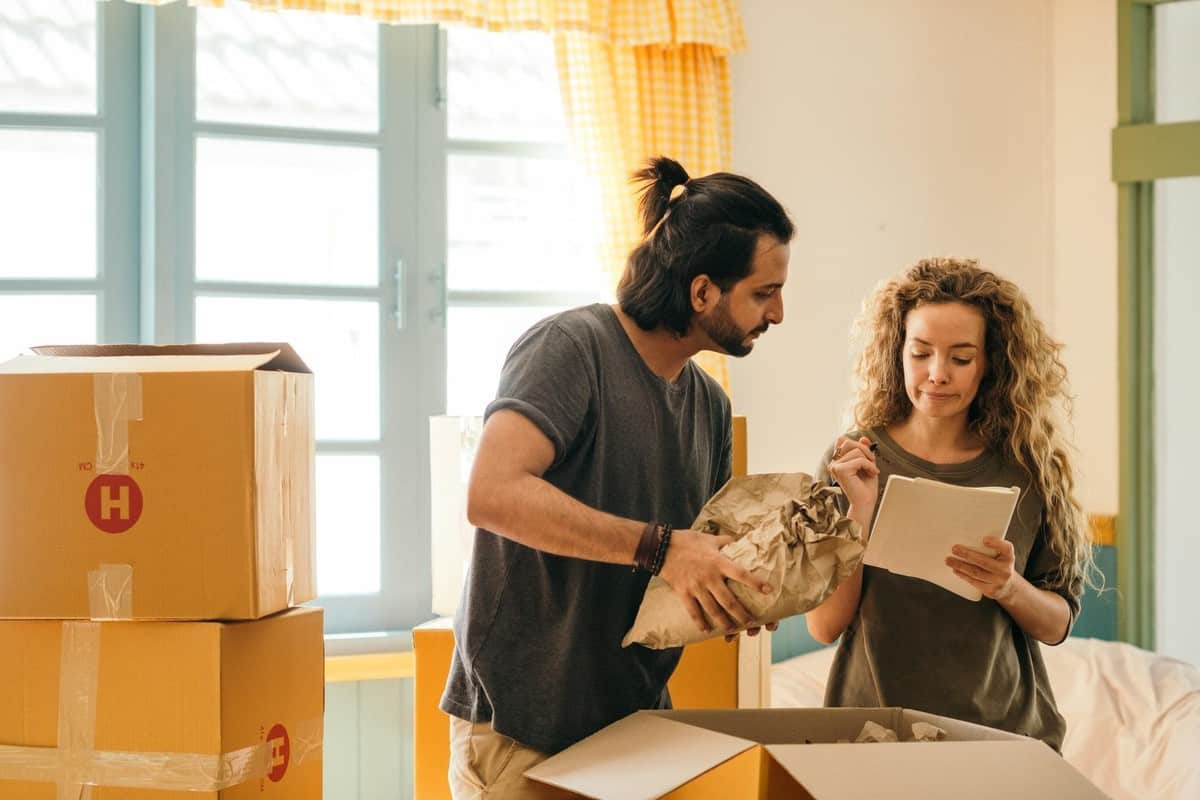 son packing with mom crossing off list as he begins moving out of his parents' house