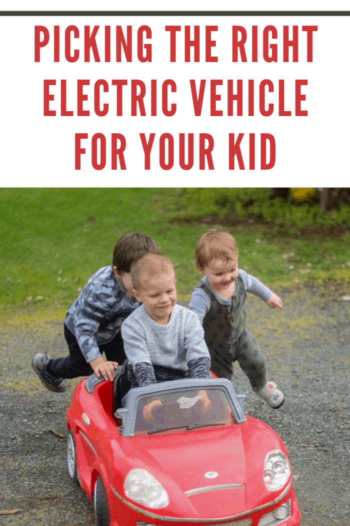child in red electric car being chased by two small boys