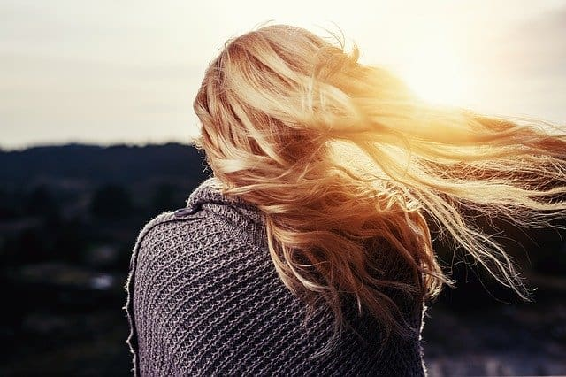 woman with blonde hair blowing in wind with grey sweater on