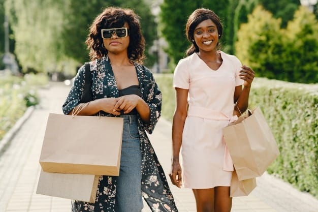Two afro american women friends in the city, wearing quality human hair lace wigs. Friends on a shopping trip carrying colorful shopping bags.