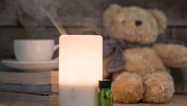 Ultrasonic humidifier on a wooden table, aroma maker in a home