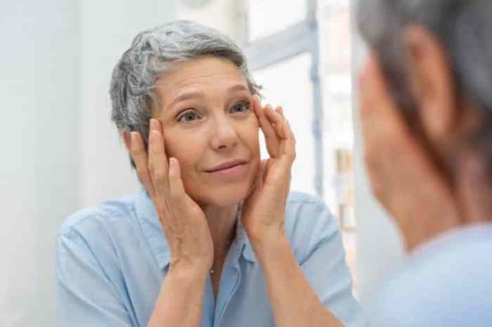 Beautiful senior woman checking her face skin and looking for blemishes. Portrait of mature woman massaging her face while checking wrinkled eyes in the mirror. Wrinkled lady with grey hair checking wrinkles around eyes, aging process. wondering at what age most health problems start