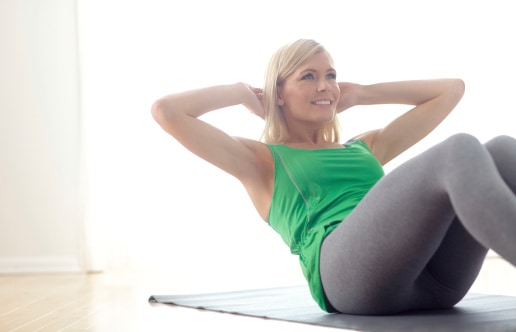 Attractive young blonde busy mom who want to get in shape exercising at home