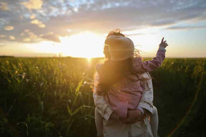 mom holding toddler with sunburst shining from the horizon