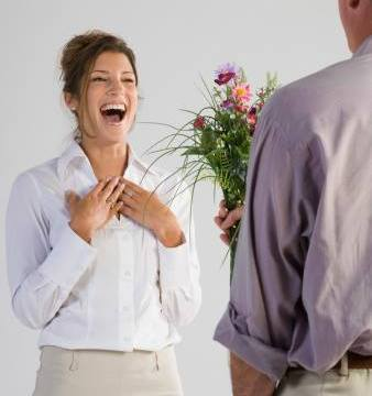 Surprised woman receiving flowers from man