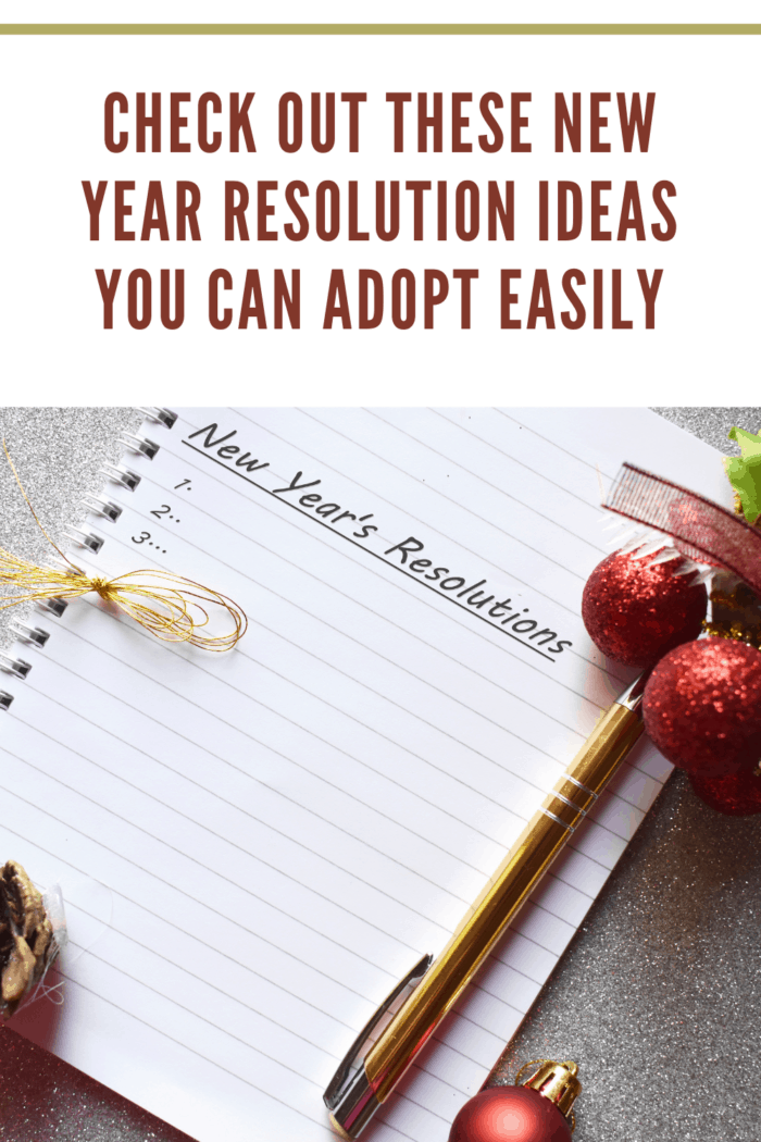 new year's resolutions written on paper in notebook with red glitter balls