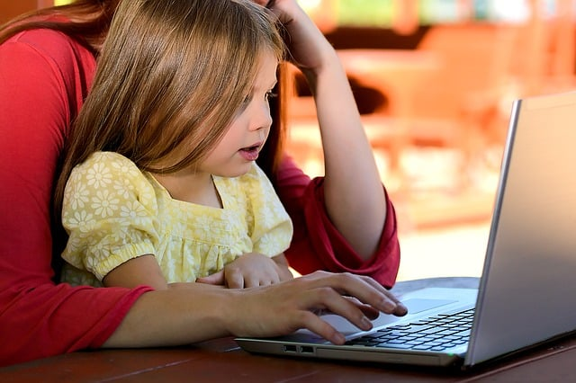 girl sitting on lap of working parent
