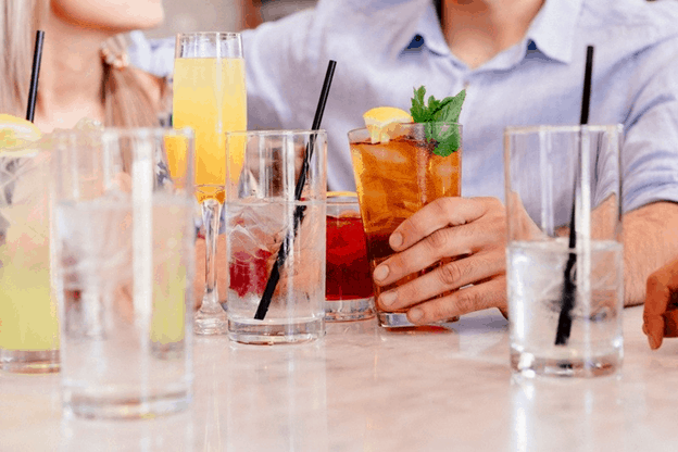 empty mixed drink glasses with man reaching for new mixed drink