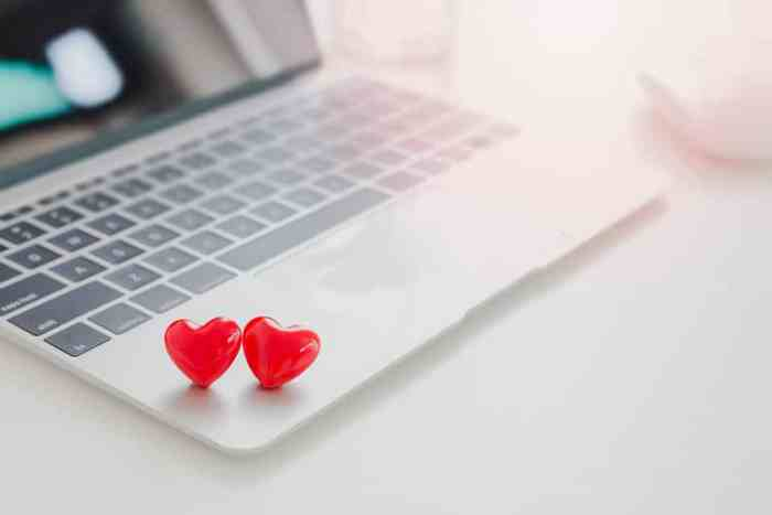 Couple red hearts on laptop on white table in office.Concept of Online dating.