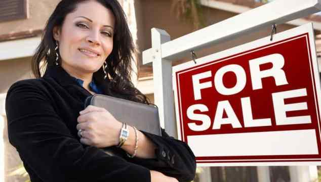Proud, Attractive Hispanic Female Agent In Front of For Sale Real Estate Sign and House