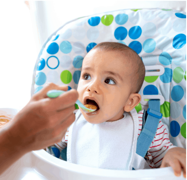 Caring parent taking responsibility of introducing her child to solid foods and teaching him that milk is not the only food in the world