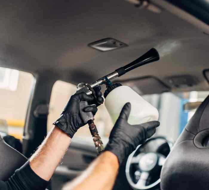 Carwash service, male worker in gloves using special spray. Professional dry cleaning of car ceiling covering, vehicle interior hygiene