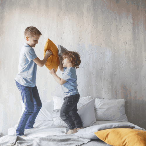Full length side view outgoing boy playing with cheerful little brother with cushions. Happy boys having fun concept