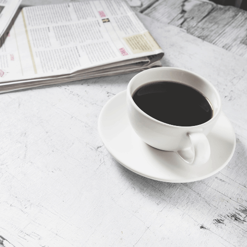 Coffee cup and morning newspaper