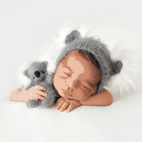 resting newborn in little cute grey hat and with grey toy bear in his hands on white background