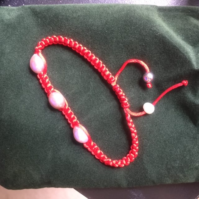 Anthony Dreyer Collection Cultured Pearl Macrame Bracelet in red resting on pouch