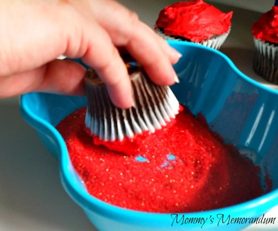 dip the cupcake into the red sugar