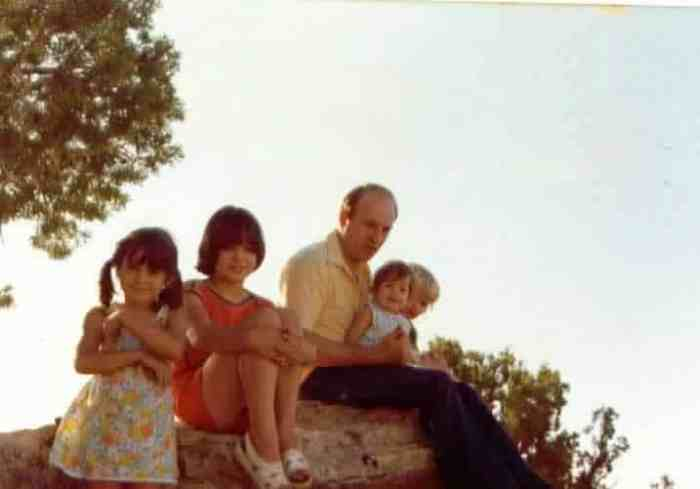 fathers and daughters sitting on rock