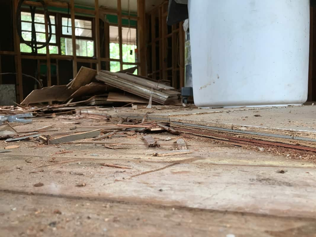 dad's house home remodel using crow bar to remove layers of flooring