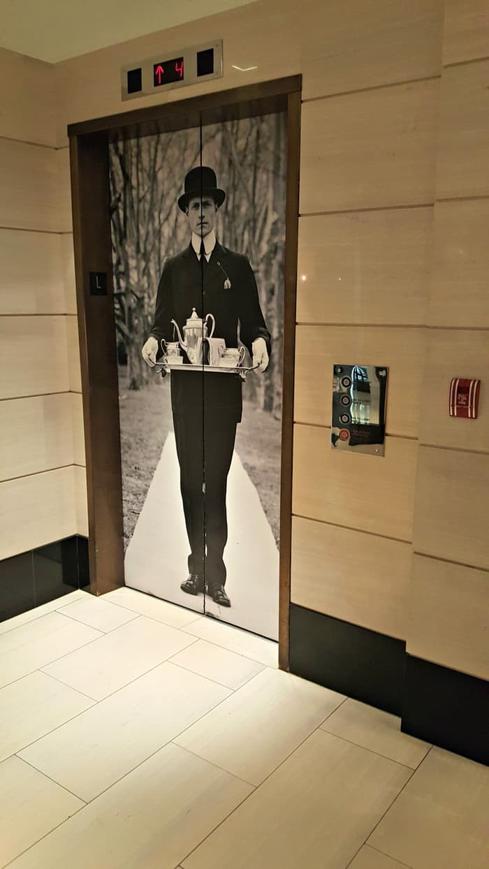 london hotel elevator man with bolo hat