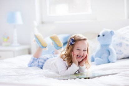 Little Girl Playing With Toy And Reading A Book In Bed in decorating your toddler's room