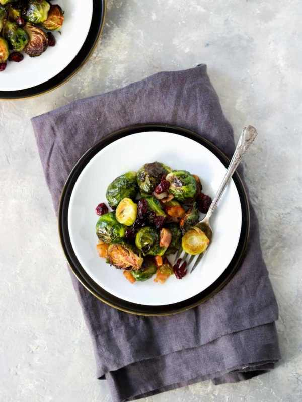 black and white plate with brussels sprouts and a fork, sitting on a gray napkin