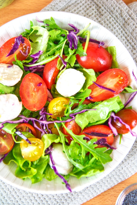 Best Summer Salad recipe is made with grape tomatoes, mini mozzarella cheese, arugula, romaine lettuce, red cabbage, all tossed in a zesty lemon poppy seed dressing.