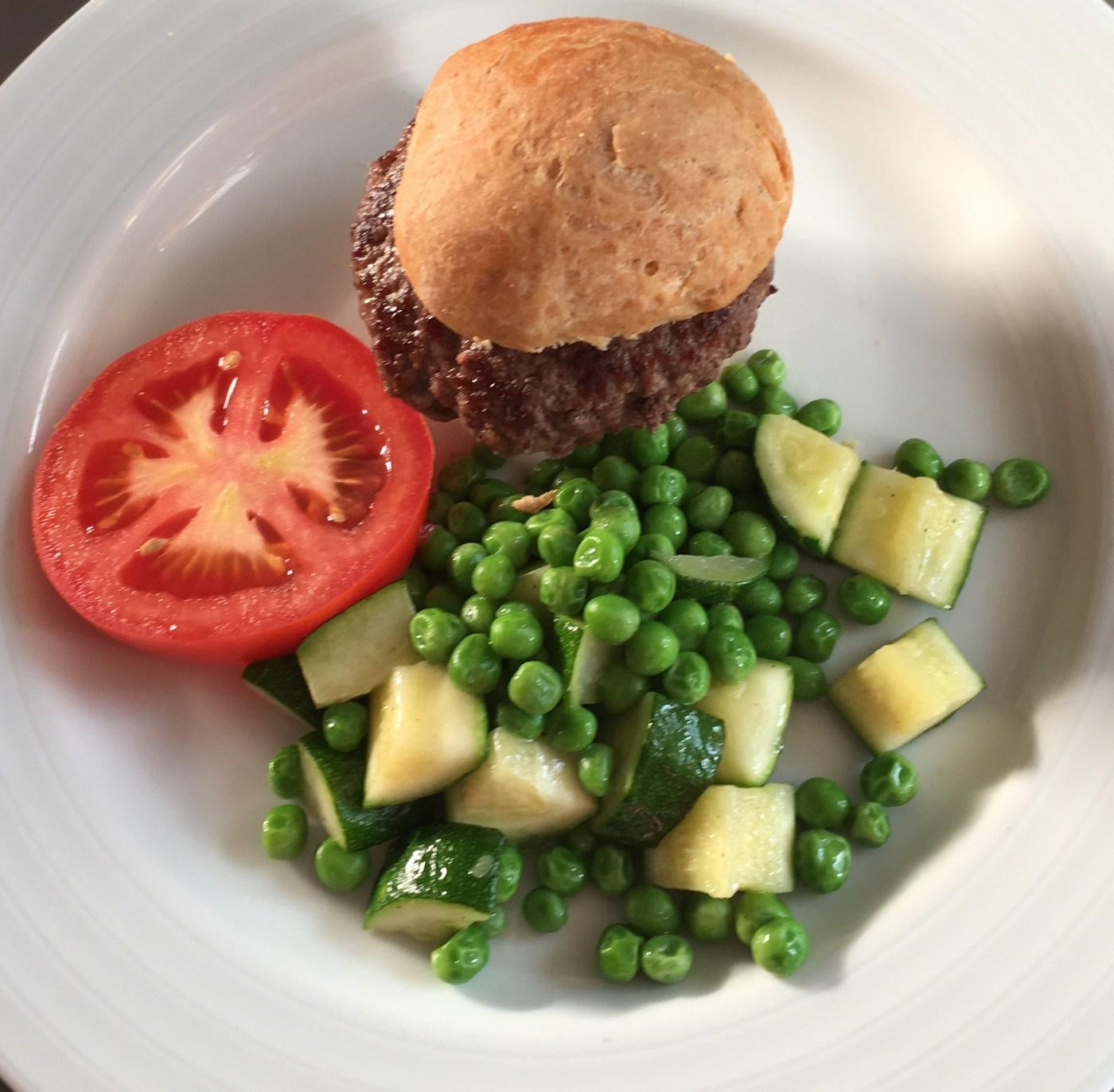 Beef burger on a wheat bun with Zucchini & Pea Salad