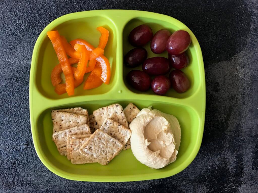 Hummus snack plates are perfect for a shareable lunch or snack. Just serve your favorite hummus alongside fresh dippers like pepper or cucumber strips and crackers.