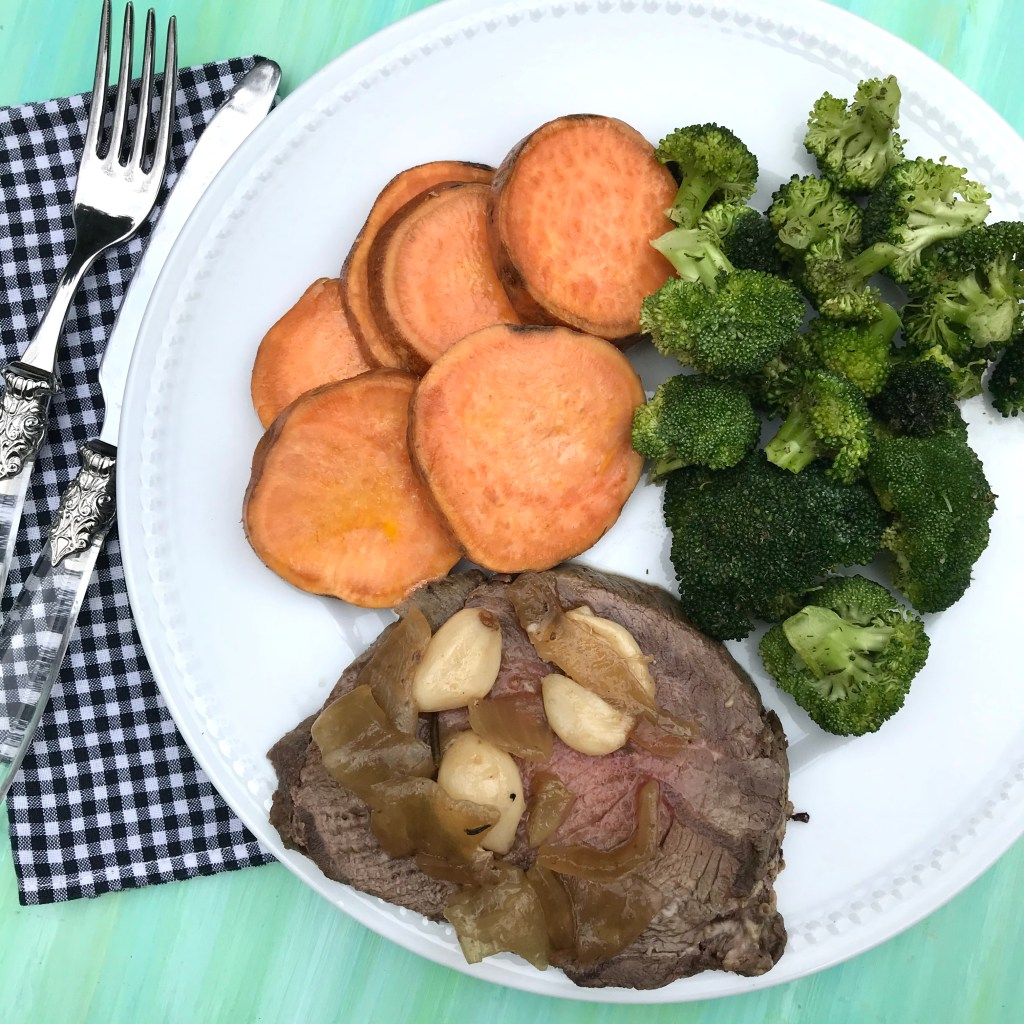 40 cloves of garlic beef roast sliced on a white plate with sweet potatoes and broccoli.