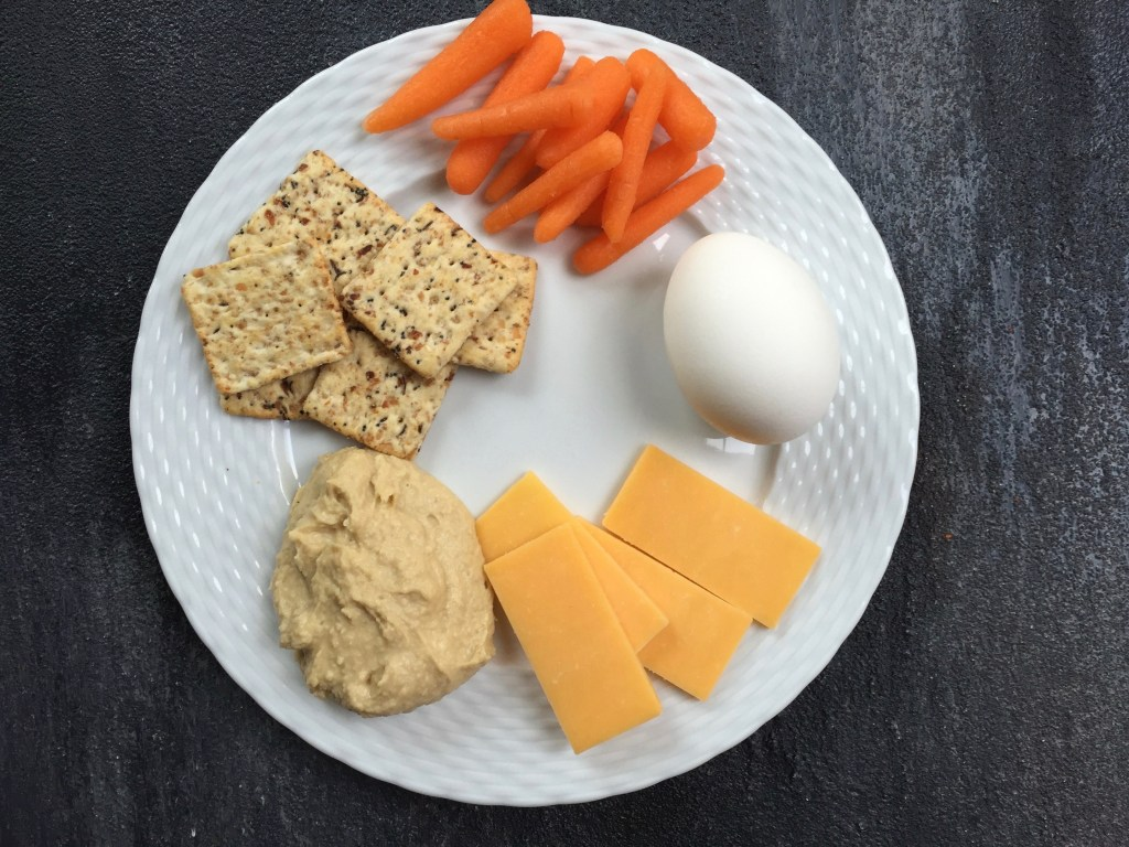 Toddler snack ideas, crackers, carrots, eggs, cheese, and hummus on a plate.