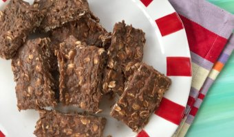 No-bake chocolate protein bars stacked on a white and red plate.