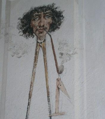 Georges Clairin, caricatura dell'architetto parigino Charles Garnier, con pipa e corpo realizzato da un compasso, affrescata nel vestibolo della Villa Garnier di Bordighera