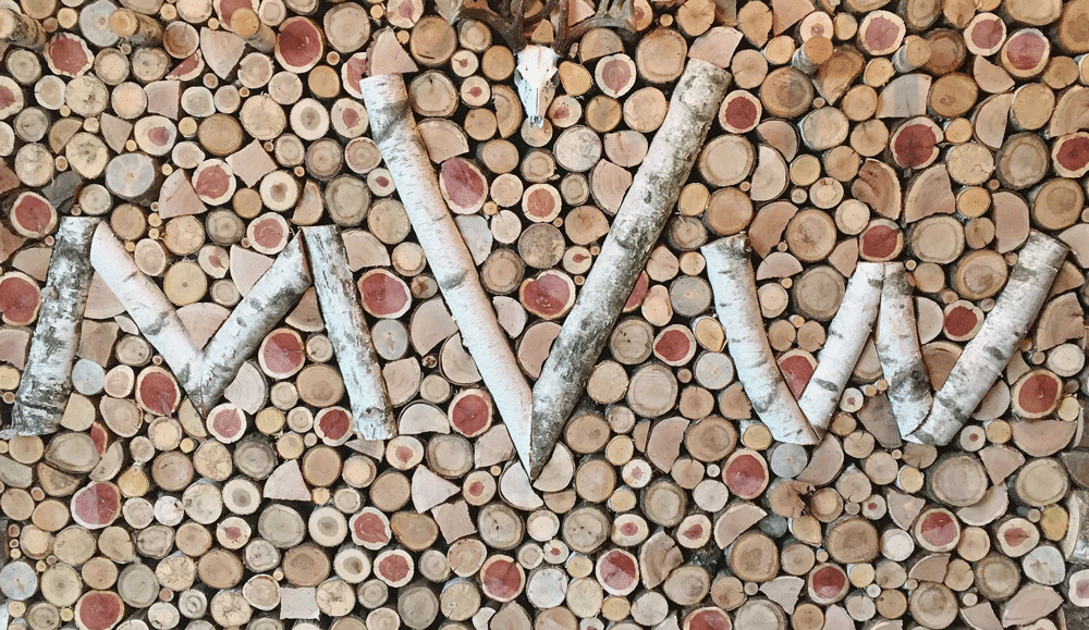"A wall of wood ends with an ""MVW"" pattern in wood"