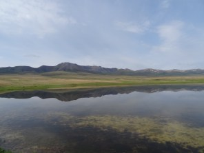 A pond shows the reflection of the mountains at Song-Kul