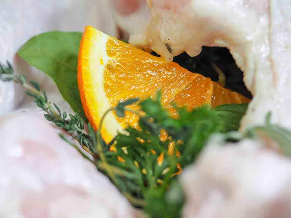 quartered orange and herbs stuffed in turkey cavity, close view