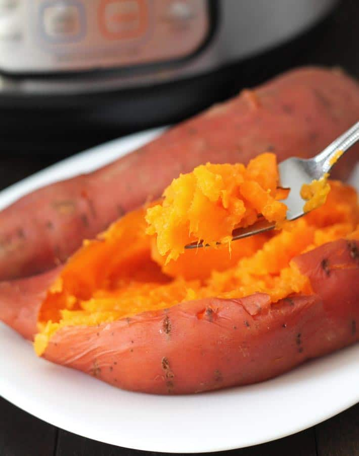 Cooked sweet potato on a white place with an Instant Pot in the Background with a bite of sweet potato on a suspended fork