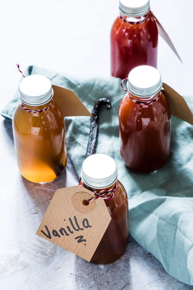 bottles of homemade vanilla extract on a woodend table with green cloth