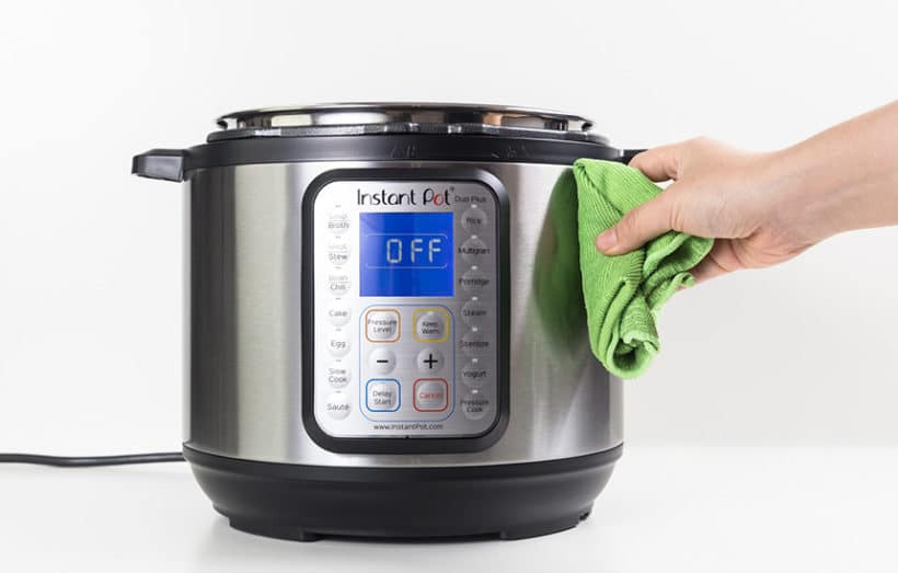 pressure cooker being cleaned with a green cloth on a white background