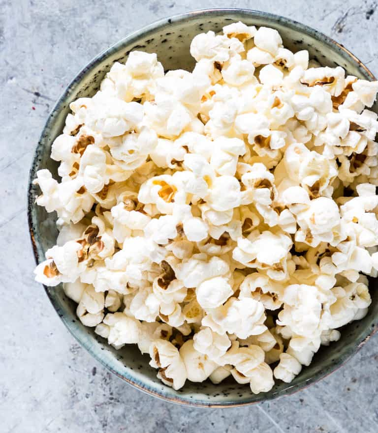 close-up of popcorn in a rusting white bowl with blue design on a marble table