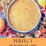 pumpkin pie on a rustic table surrounded by fall leaves and pumpkins
