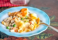 baked chicken pot pie on a blue edged ribbon plate on a table with a fork