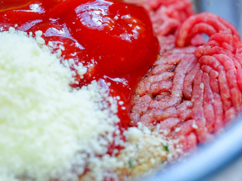 ground beef with ketchup parmesan cheese with spices for a meatloaf mixture in a bowl