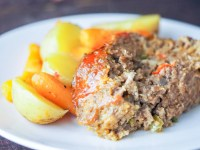 sliced meatloaf on a white plate with roasted potatoes and carrots