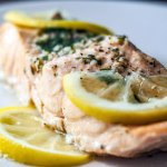 steamed herbed salmon on a plate with lemon slices