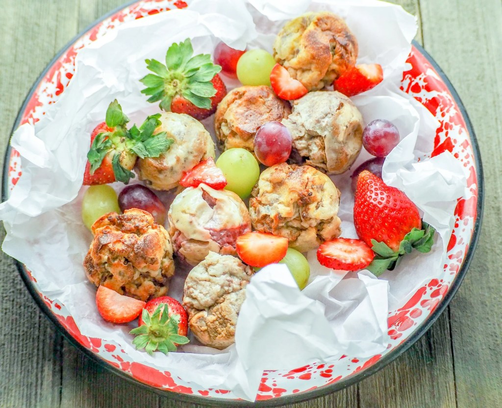 french toast bites on a red and white metal pie plate with crumpled parchment paper with grapes and strawberries