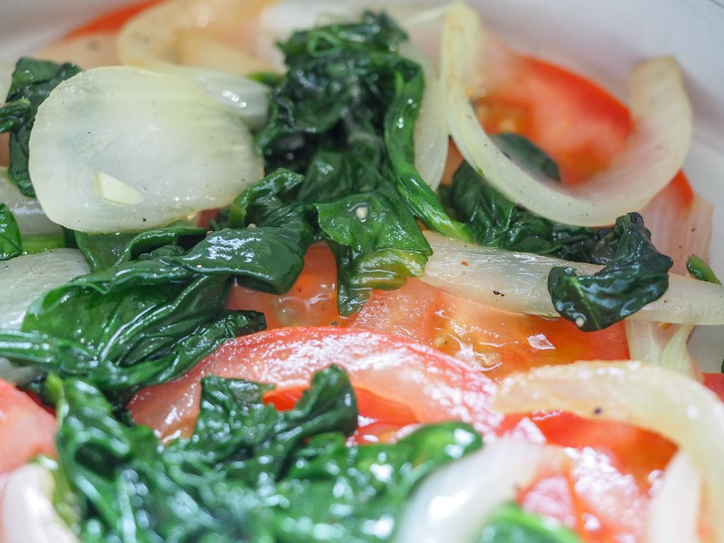 sliced tomatoes with cooked spinach and sliced onions arranged in the bottom of a pan