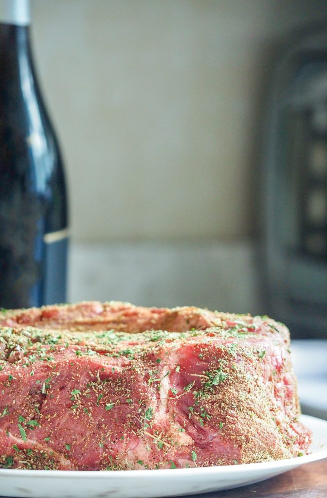 raw beef chuck roast coated in dry rub on a white plate on top of a cutting board with bottle of wine in the background