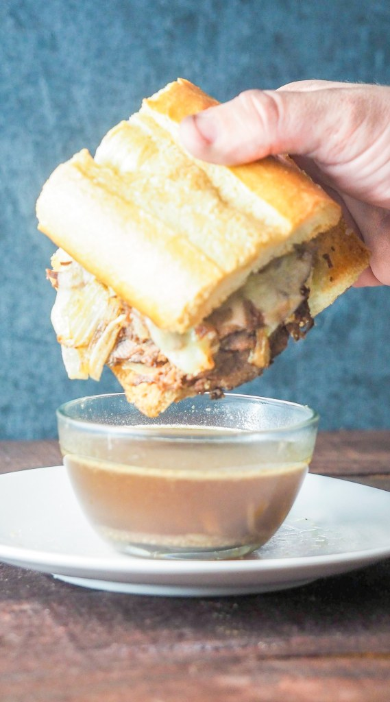 french dip sandwich being held above a bowl of au jus gravy