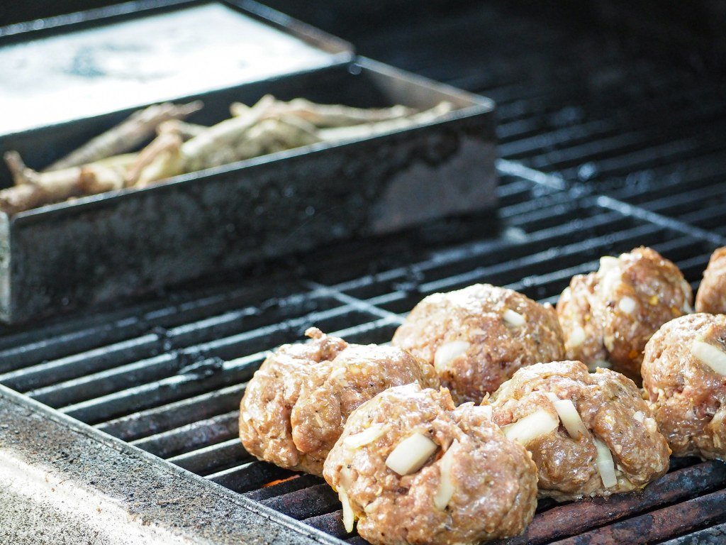 meatballs on grill rack with smoker box to the left